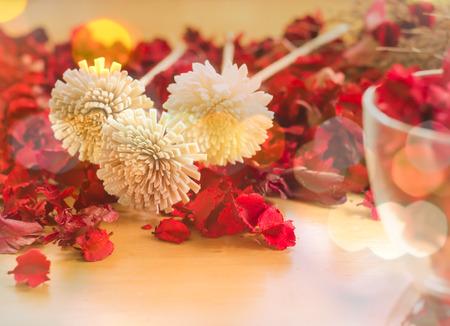 flores secas: Marr�n flores secas en la hoja de color rojo sobre un fondo placas de madera y Boke iluminaci�n de efecto.