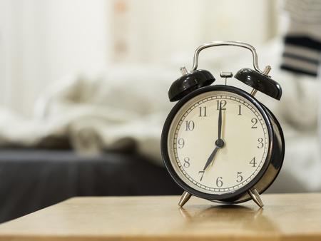 Retro schwarze Wecker zeigen 7 Uhr morgens für Wake up.Background ist ein Schlafzimmer. Standard-Bild - 39986788