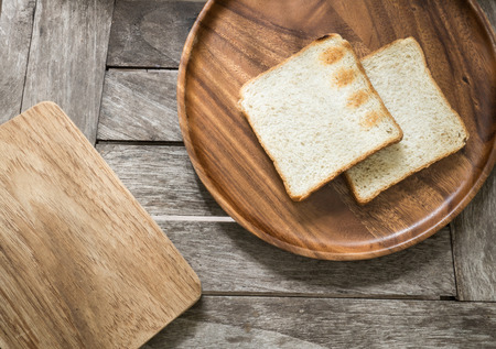 Toast bread on wooden plate and wooden breadboard on wood background photo