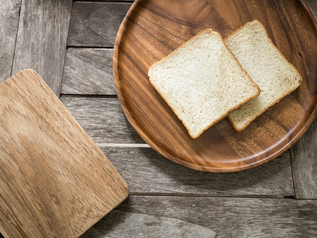 breadboard: Toast bread on wooden plate and wooden breadboard on wood background Stock Photo
