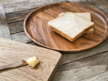 breadboard: Toast bread on wooden plate and wooden breadboard with butter on wood background