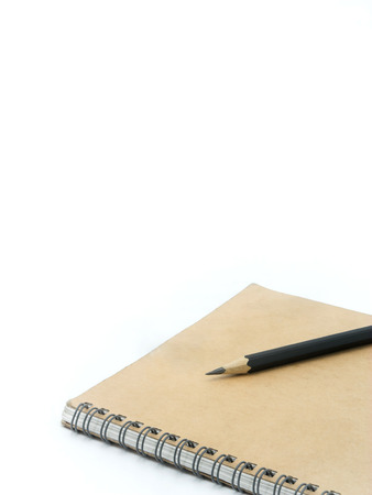 composition notebook: Black pencil on a brown notebook in white background ( Space and Composition for text ) Stock Photo