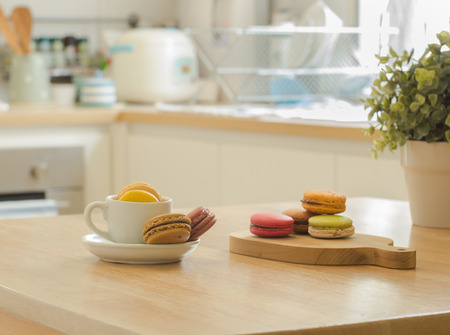 Colorful French macarons cookie in cup and wooden tray on wooden table in a kitchenoden table in a kitchen