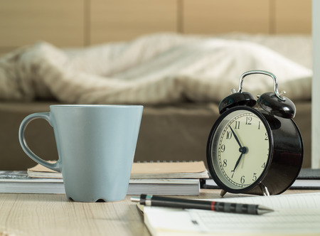 Cup mug and book, pencil, retro alarm clock on the table in bedroom. ( Vintage tone color) Stock Photo