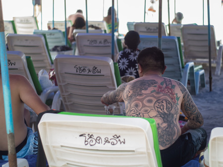 wean: KOH LAN, PATAYA, THAILAND- JUNE 20:Tattoo Chinese tourist in Ta wean beach at Koh Lan Island.Koh Lan is wonderful beaches and the most popular for tourists frequently visited. PATTAYA, THAILAND, JUNE 20,2015