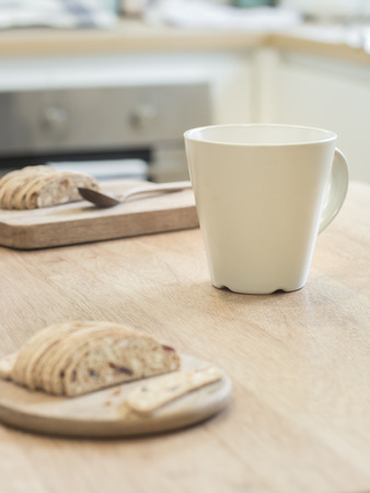 almond biscuit: White cup and slice almond  biscuit cookie on wooden tray Stock Photo