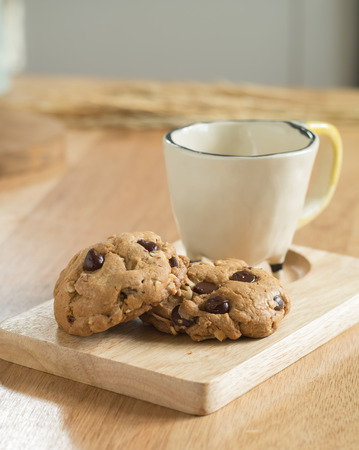 milk and cookies: Chocolate chip cookies on wooden tray