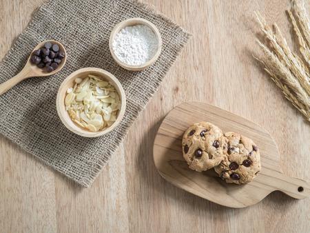 Draufsicht Chocolate Chip Cookies und Zutat auf Sack und Tablett aus Holz auf Holztisch Standard-Bild - 43638678