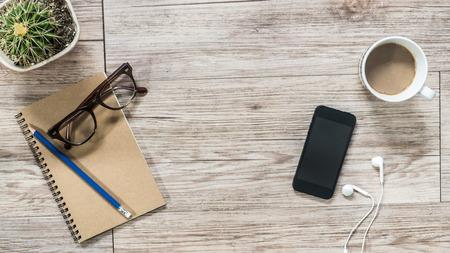 Entspannen Sie sich am Arbeitsplatz - Draufsicht auf Smartphone mit leeren Bildschirm, Kopfhörer, Notebook und Kaffee auf Holzuntergrund (Raum und Komposition für Text) Standard-Bild - 44253650