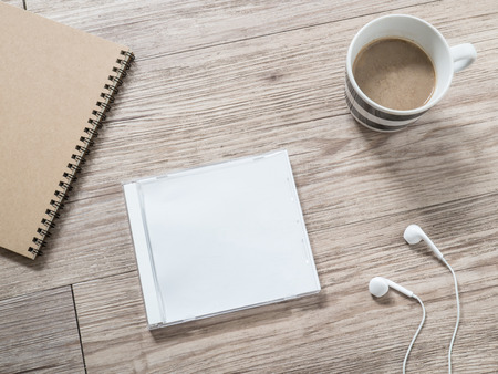 cover: Top view of blank compact disc (CD) with cover , earphones, notebook and coffee on wooden background Stock Photo
