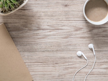 earbuds: Top view of earphones,notebook and coffee on wooden background ( Space and composition for text )