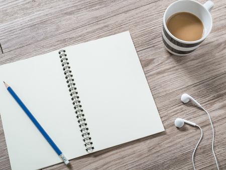 Top view of  notebook with blank screen, pencil ,earphones,and coffee on wooden background ( Space and composition for text )
