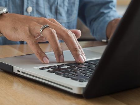 teclado de computadora: El hombre joven manos usando la computadora portátil teclado de la computadora en el escritorio de madera. Foto de archivo