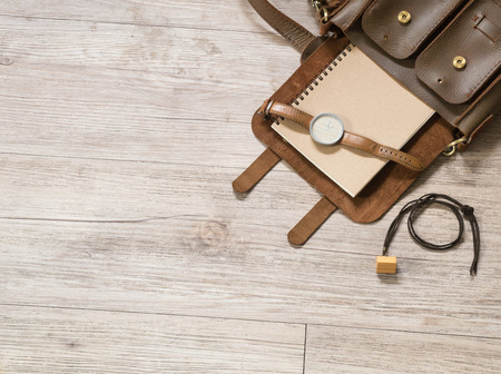 leather bag: Women accessories in small  leather bag,  watch, notebook and leather necklace on wooden background ( Composition and space for text )