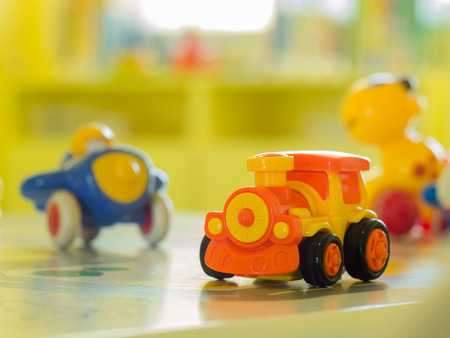 toy car: children toys - Orange plastic toy engine train and another toy  on a table