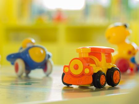carritos de juguete: juguetes de los ni�os - tren motor de juguete de pl�stico naranja y otro juguete en una mesa Foto de archivo