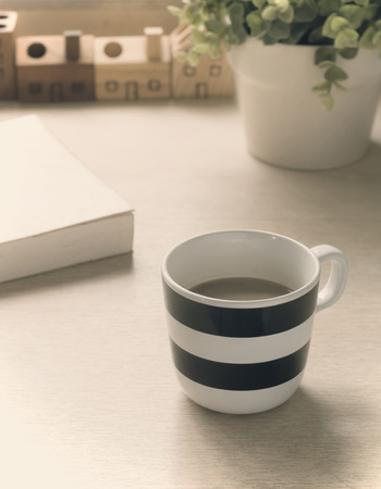 vigorously: Stripped cup of coffee and a book on a wooden table ( Vintage tone color ) Stock Photo