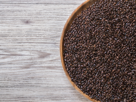 Top view - Beer ingredient, Chocolate malt in wooden plate and on wooden background
