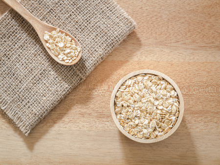 Top view -  Wheat flakes in wooden bowl on wooden background - Raw food ingredients