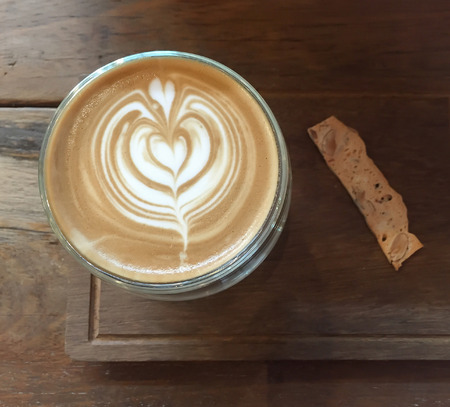 Top view of  latte art coffee and cookie snack  on wood background Фото со стока