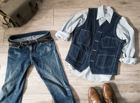 Top view - Vintage male clothing ( Shirt , Navy vest , jeans )and accessories on the wooden background  Фото со стока