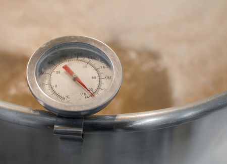 Stainless steel kitchen thermometer measures the temperature of boiling wort beer homebrew ( warm tone color )  Фото со стока