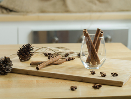 Cinnamon sticks in glass on wooden board