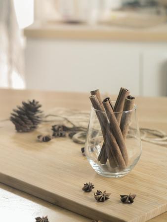 Cinnamon sticks in glass on wooden board ( Vintage tone color )