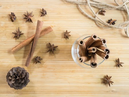 Top view - Cinnamon sticks in glass on wooden board Stock Photo
