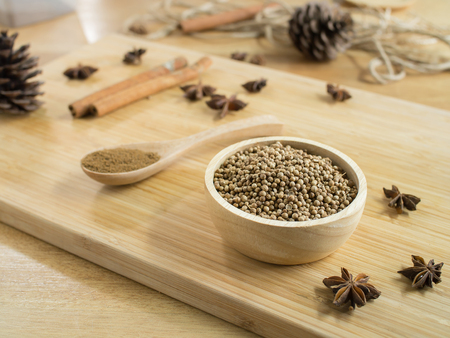 Coriander seeds in wooden bowl  and on wooden board. Фото со стока - 77453191