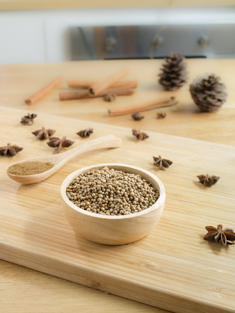 Coriander seeds in wooden bowl  and on wooden board.