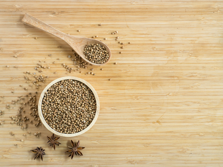 Coriander seeds in wooden bowl  and on wooden board.( Space and composition for text )