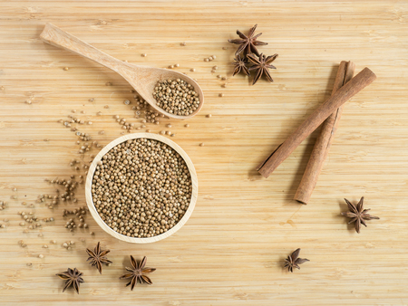 Top view - Coriander seeds in wooden bowl  and on wooden board.