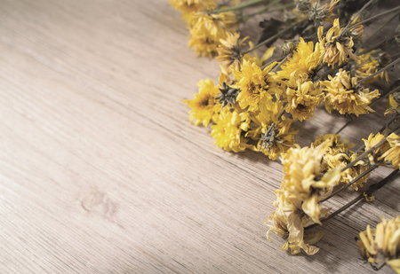 Yellow dried flowers on rustic wooden planks background- Vintage tone color ( Space and composition for text )