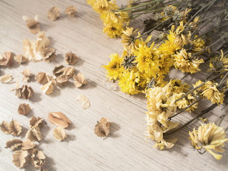 Yellow dried flowers on rustic wooden planks background ( Vintage tone color )