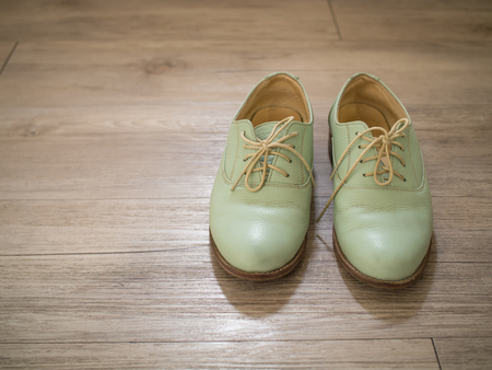 Vintage retro a pair of women green leather shoes on a wooden floor ( Vintage tone color ) Stock Photo