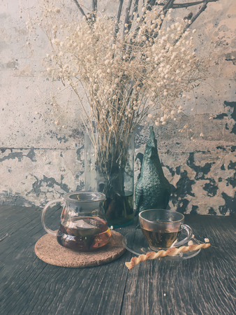 Glass jug and cup of tea on wooden table decorate with dried flowers ( Vintage tone color ) Stock Photo