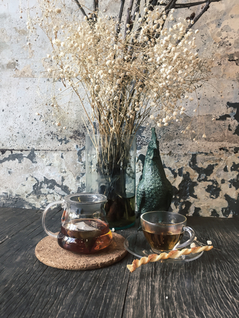 Glass jug and cup of tea on wooden table. Decorate with dried flowers in front of aged cracked concrete  wall. Фото со стока