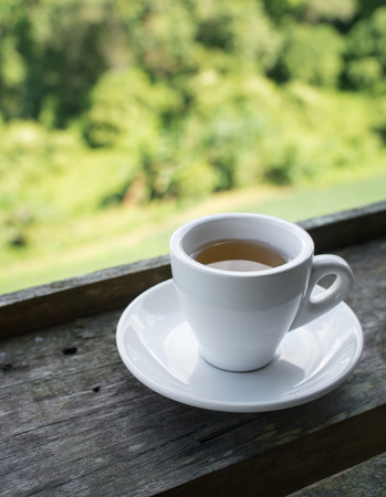 Cup of tea on wooden bar. Beauty nature background of mountains and tea plantation landscape  at Doi-Montngo , Chiang Mai, Thailand Фото со стока - 79703878