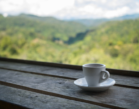 Cup of tea on wooden bar. Beauty nature background of mountains and tea plantation landscape  at Doi-Montngo , Chiang Mai, Thailand