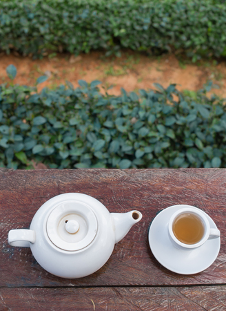 Top shot - Cup of tea and teakettle on wooden bar. Beauty nature background of tea plantation  at Doi-Montngo , Chiang Mai, Thailand Stock Photo