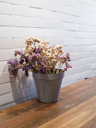 dried flowers in flowerpot  on wooden table