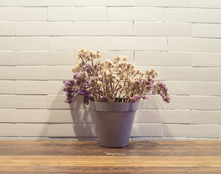 dried flowers in flowerpot  on wooden table ( Vintage tone color )