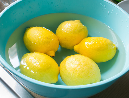 Fresh lemon in a blue bowl with water