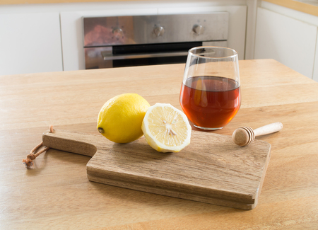 Honey lemon - lemon on chopping board and Glass of honey and honey dipper on wooden table
