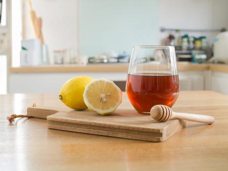 Honig-Zitrone - Zitrone auf Schneidebrett und Glas Honig und Honigschöpflöffel auf Holztisch Standard-Bild - 89469968