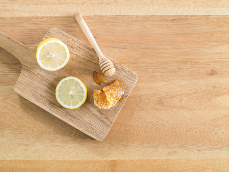 Top view - Lemon and honey dipper on chopping board and  on wooden table ( Space and composition for text background ) Фото со стока