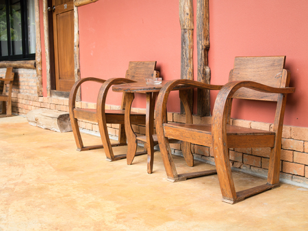 Holztisch und Stuhl vor einer Wand Standard-Bild - 93945846