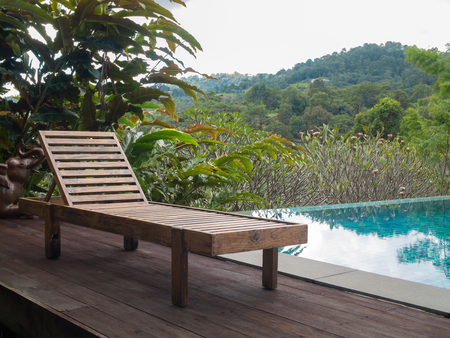 Wooden pool chair at the resort with beautiful landscape of countryside mountain view