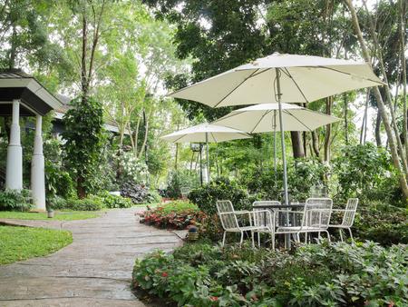 Tisch und Stuhl im Freien mit Regenschirm im grünen Garten Standard-Bild - 94136828